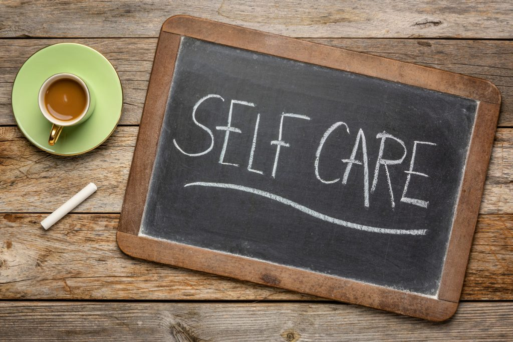 A cup of tea next to a chalkboard with the word Self-care on it